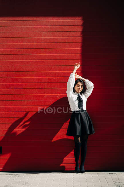 Full body of female with arms raised looking down while standing against red gates — Stock Photo