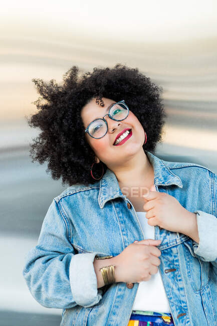 Adult overweight female in trendy clothes and eyewear with Afro hairstyle looking at camera on blurred background — Stock Photo
