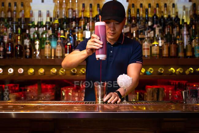 Молодий азіатський бармен поливає полуничний сік у коктейль, готуючи коктейль у барі. — стокове фото