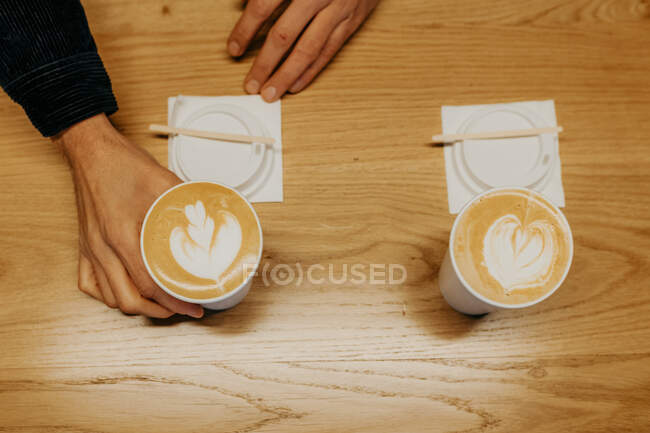 From above of crop unrecognizable person taking takeaway cup of coffee with latte art placed on wooden table in cafe — Stock Photo
