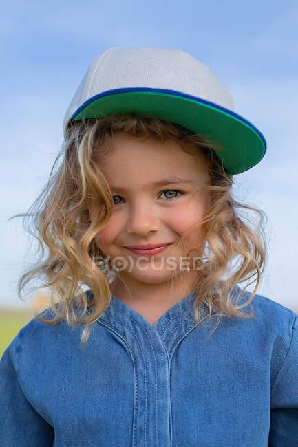 Счастливая девушка в стильной одежде и кепке смотрит в камеру, стоя на траве в солнечный летний день в поле — стоковое фото