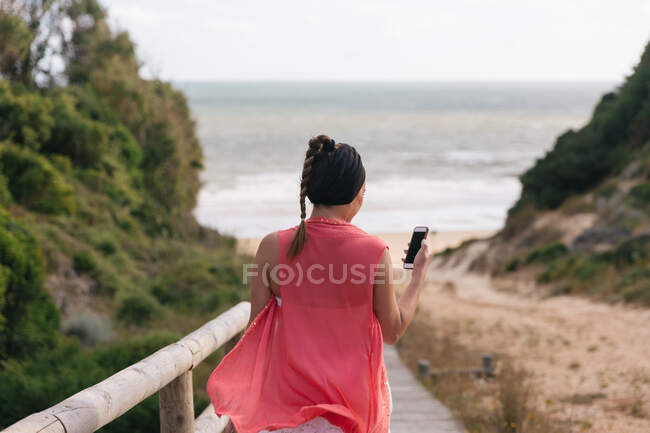 Back view of anonymous female in pink silky blouse using mobile phone with black screen on coast of sea — Stock Photo