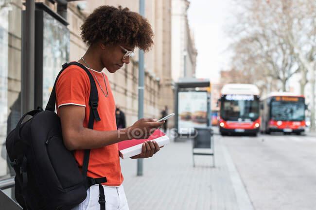 Vista lateral del joven afroamericano con ropa casual y mochila usando un teléfono inteligente mientras está de pie en la calle de la ciudad y esperando el autobús - foto de stock