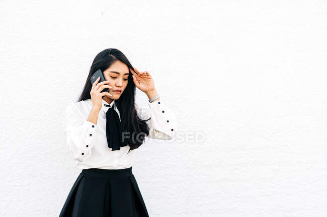 Teen ethnic Asian female in formal outfit standing near white wall speaking on the mobile phone — Stock Photo