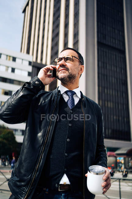 Mature Hispanic male executive in smart casual wear with hot drink to go talking on cellphone while walking on urban pavement — Stock Photo