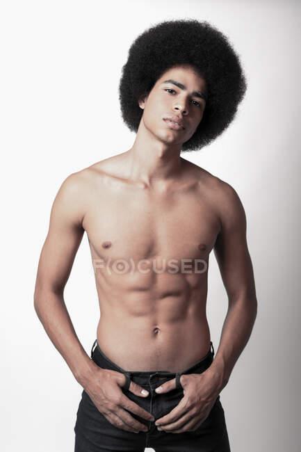 Joven hombre negro confiado con seis abdominales paquete y peinado afro mirando a la cámara sobre fondo blanco - foto de stock