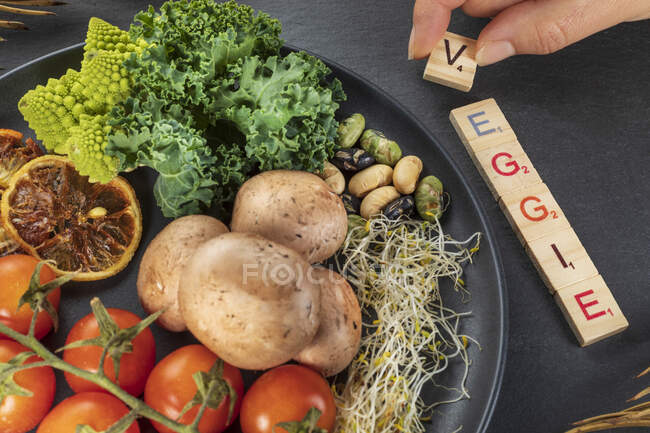 Top view of anonymous cook compiling decorative title near assorted vegetables and fruits with nuts on plate on gray background — Stock Photo