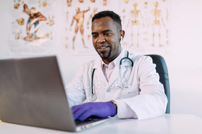 Médico masculino afroamericano concentrado joven en bata médica y auriculares TWS que trabajan en el ordenador portátil mientras está sentado en la mesa en la clínica moderna - foto de stock