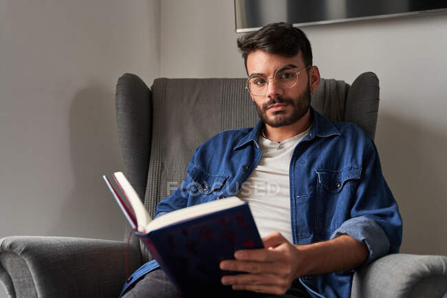 Concentrated young Hispanic guy in casual clothes sitting in comfortable armchair and reading interesting book and looking at camera in daylight at home — Stock Photo