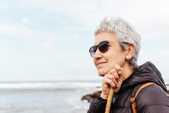 Side view of smiling elderly female trekker in sunglasses with gray hair looking away against stormy ocean — Stock Photo