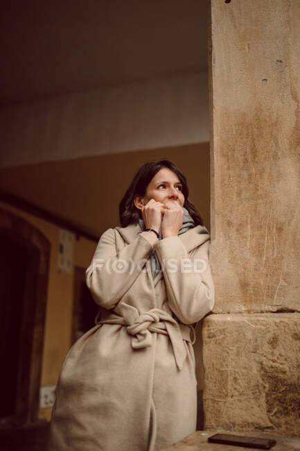 Young shy female in outerwear touching face while looking away in aged construction in daylight — Stock Photo