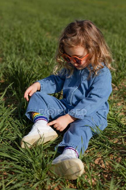 Високий кут гарної щасливої дитини сидить на зеленому полі в сонячний день граючи з травою влітку. — стокове фото