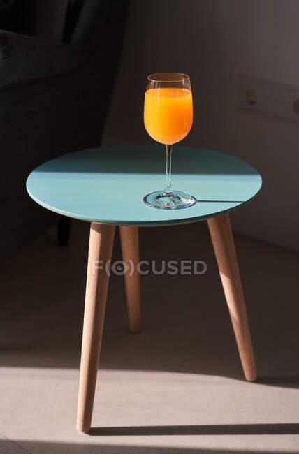 Сверху стакана свежего апельсинового сока, размещенного на небольшом круглом столе рядом с удобным диваном под солнцем — стоковое фото