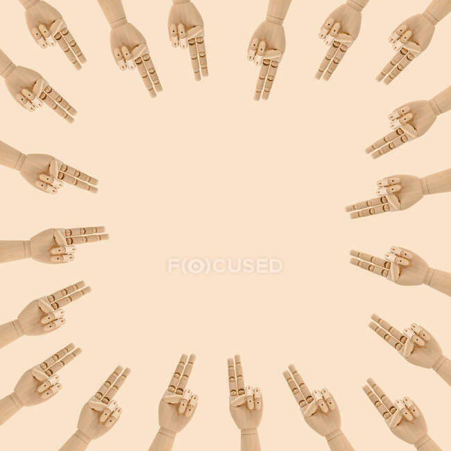 From above of composition of wooden hands with index and middle finger together gesture placed in circle and pointing in center against beige background — Stock Photo