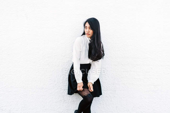 Teen Asian woman with long hair adjusting stockings while leaning on wall and looking away — Stock Photo