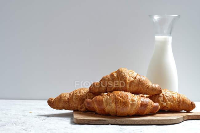 Смачні круасани та пляшка молока клали на стіл на сніданок на кухні. — стокове фото