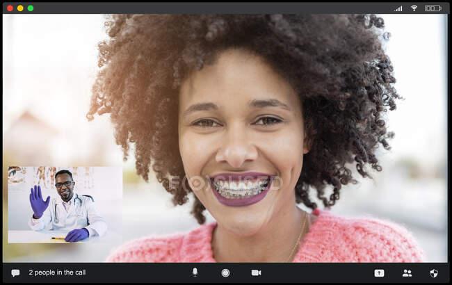 Цінні афроамериканські пацієнтки з брекетами посміхаються перед камерою, розмовляючи з лікарем, який махає рукою під час відеобесіди. — стокове фото