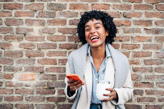 Delighted African American female with curly hair standing with cup against brick wall and browsing mobile phone — Stock Photo