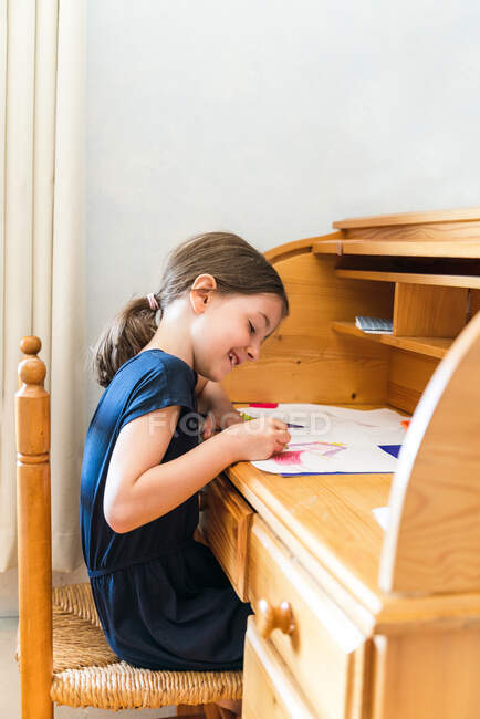 Side view adorable happy girl in casual wear drawing pictures on papers and sitting at desk at home — Stock Photo