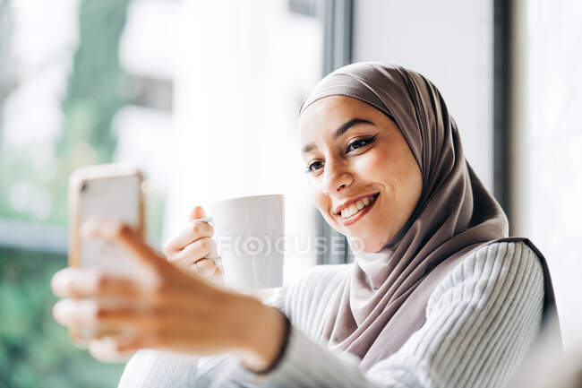 Glad ethnic female in hijab and with cup of drink taking selfie on smartphone while enjoying weekend in cafe — Stock Photo