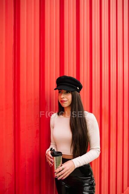 Mujer de negocios segura en ropa de moda de pie con bebida para ir en la ciudad en el fondo de la pared roja y mirando hacia otro lado - foto de stock