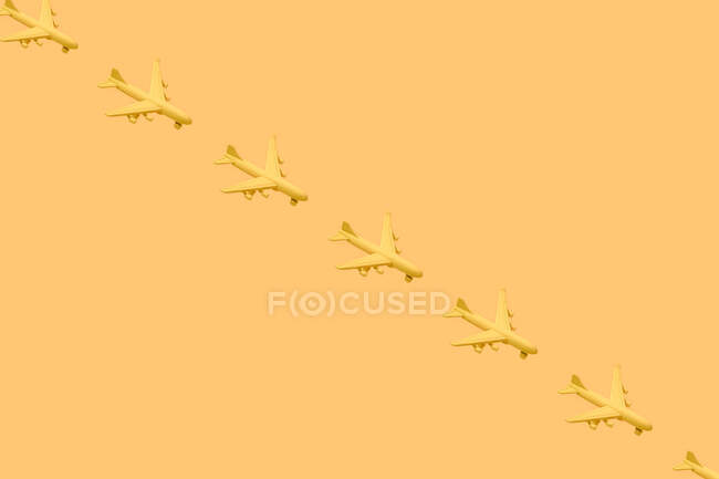 From above of composition of many little yellow airplanes placed against yellow background in studio — Stock Photo