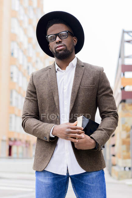 African American male in stylish hat and jacket standing on city street and holding book — Stock Photo