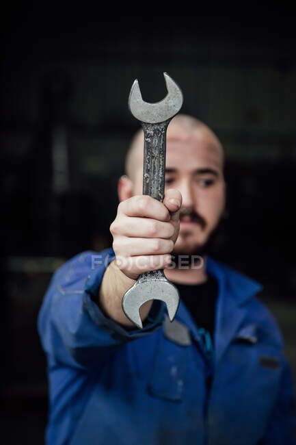 Male mechanic in blue overall covering face with metal spanner in hands looking away on black background — Stock Photo