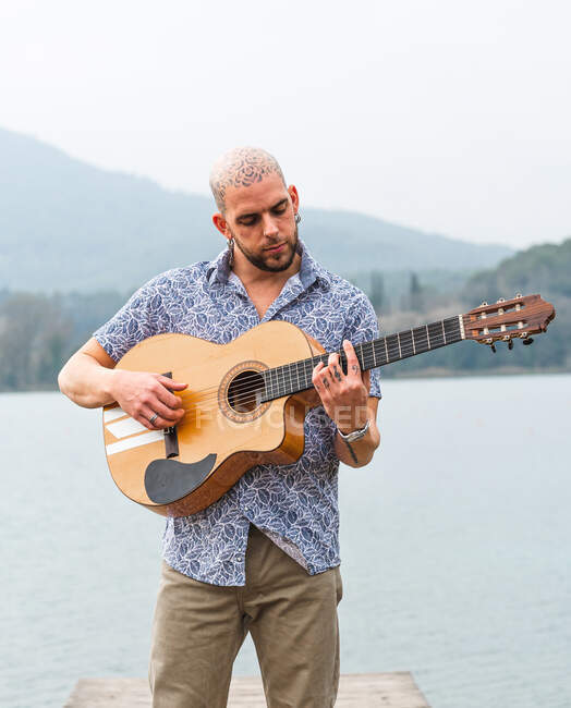 Bearded guy in casual clothes standing with guitar on wooden pier near river with mountains on background under cloudy gray sky in daytime — Stock Photo