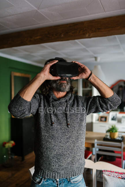 Unrecognizable unshaven male exploring virtual reality in modern headset in house room in daytime — Stock Photo
