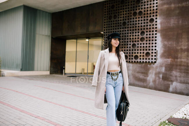 Young trendy female entrepreneur standing near entrance of contemporary building in city and looking away — Stock Photo