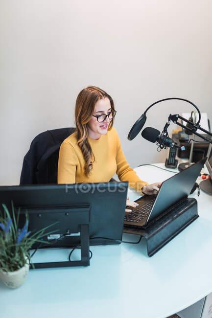 Positive weibliche Browsing modernes Netbook, während am Tisch mit Monitoren und Mikrofon während der Arbeit im Broadcast-Studio mit speziellen Geräten sitzen — Stockfoto