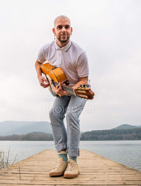Full body of bearded guy in casual clothes standing with guitar on wooden pier near grass and river with mountains on background under cloudy gray sky in daytime — Stock Photo