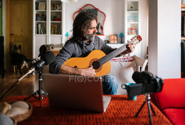 Middle aged ethnic male guitarist tuning acoustic guitar against laptop and photo camera in house room — Stock Photo