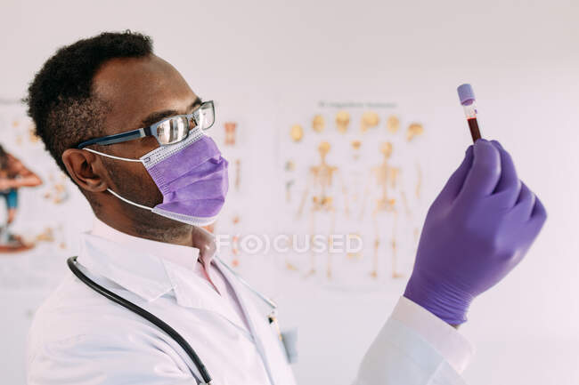 African American male doctor in medical glove demonstrating test tube with blood sample on white background — Stock Photo