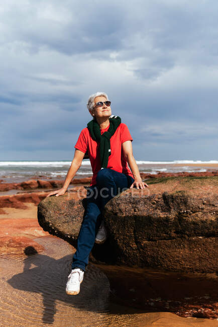 Smiling elderly female tourist in sunglasses sitting on rough boulder while looking up against ocean under cloudy sky — Stock Photo