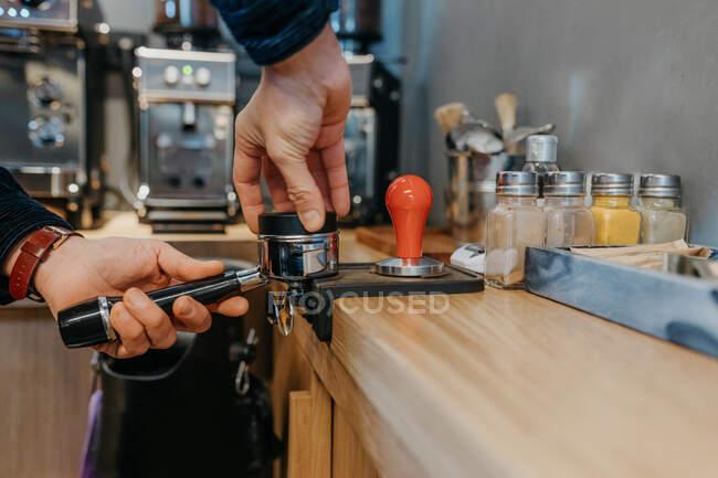 Безликий барист стоїть за столом і готує свіжу ароматичну каву, працюючи в кафетерії вдень. — стокове фото
