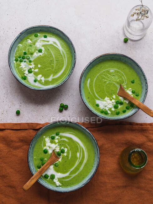 Top view of delicious pea cream soup in bowls served on table with napkin and vase with flowers — Stock Photo