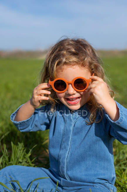 Cute happy little girl in trendy clothes and sunglasses sitting and relaxing on grassy lawn looking at camera — Stock Photo