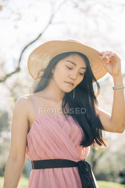 From below peaceful thoughtful ethnic female in straw hat and dress standing under blooming fragrant flowers on tree branches in orchard — Stock Photo