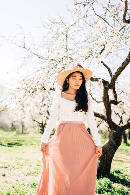 Pacifica mujer étnica reflexiva en sombrero de paja y vestido de pie bajo flores fragantes florecientes en ramas de árboles en el huerto - foto de stock