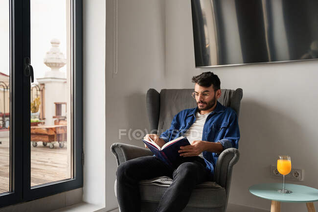 Concentrated young Hispanic guy in casual clothes sitting in comfortable armchair and reading interesting book near table with glass of fresh orange juice in daylight at home — Stock Photo