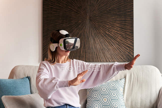 Contenida joven hembra en traje casual viendo video usando gafas VR mientras está sentada en un cómodo sofá en casa - foto de stock