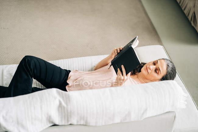 Desde arriba de libro de lectura femenina mientras está acostado en un cómodo sofá en la sala de estar con planta verde en casa - foto de stock