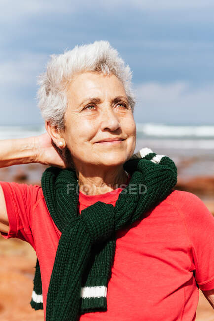 Touriste âgée joyeuse en vêtements colorés avec la main derrière la tête regardant vers le haut sur le rivage de la mer au soleil — Photo de stock