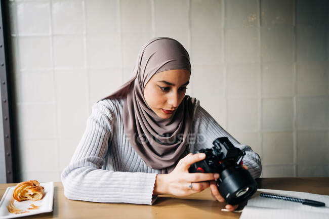 Focused Muslim female photographer sitting at table and looking through photos on professional camera while working remotely in cafe — Stock Photo