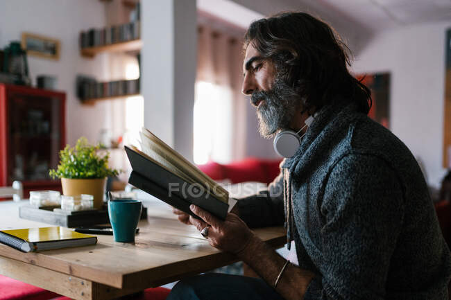 Vue latérale d'un homme ethnique d'âge moyen barbu avec un casque lisant un manuel à la maison en plein jour — Photo de stock