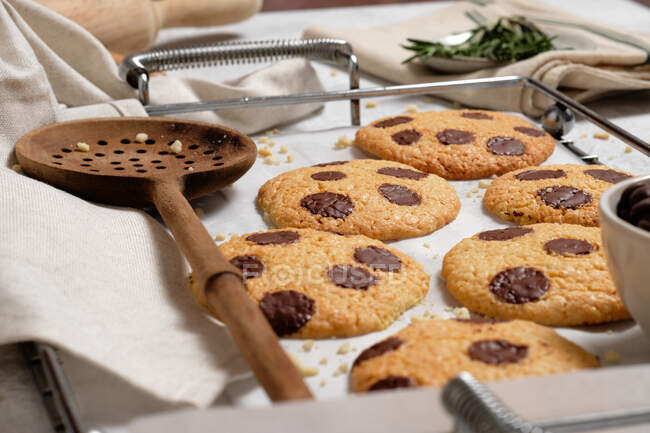 From above of freshly baked sweet cookies with chocolate chips on metal grid placed on table with various kitchen tools and green rosemary branches — Stock Photo