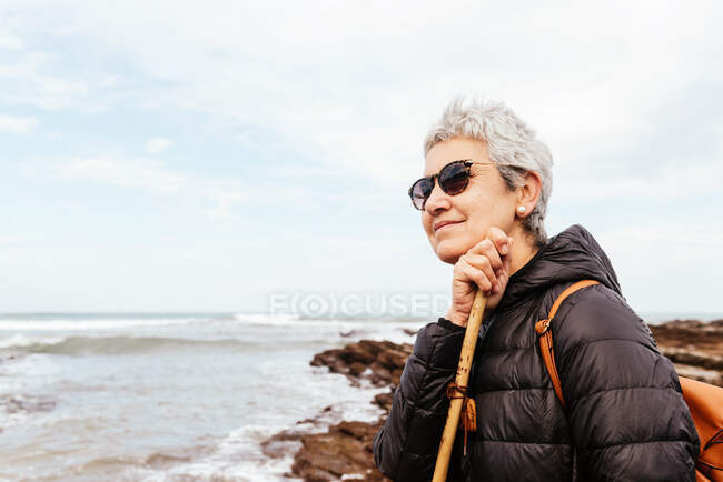 Vue latérale de trekker femme âgée souriante dans des lunettes de soleil avec les cheveux gris regardant loin contre l'océan orageux — Photo de stock