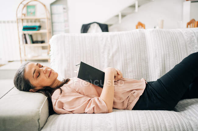 From above of sleepy middle aged female lying on comfortable sofa with plaid while resting in living room at home — Stock Photo